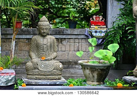 Typical Balinese (indonesian) sanctuary with statue of hindu god in the garden with flowers and offerings