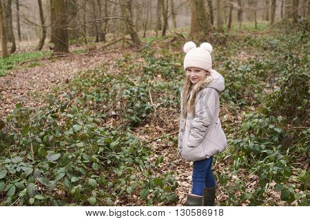 Young girl standing alone in forest undergrowth