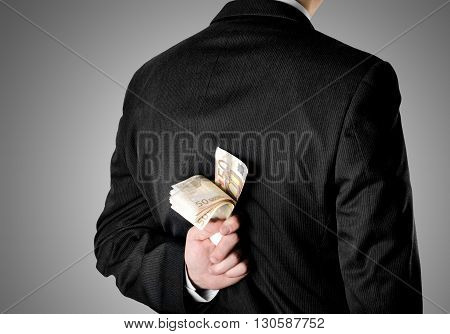 Businessman hinding fifty euro bank notes behind his back