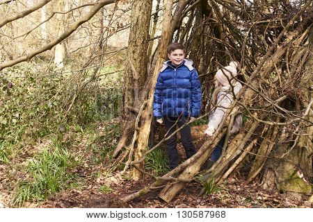 Brother and sister in a forest shelter made of tree branches