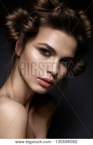 Beautiful brunette girl with a creative hairstyle and dark makeup. Art beauty, fashion model. Picture taken in the studio.