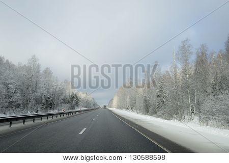 Winter road with frozen trees near of it