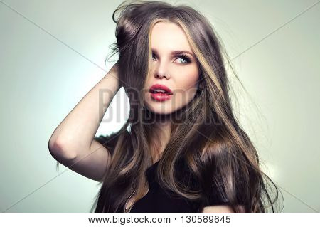 Beautiful young and emotional caucasian woman model with great hair and makeup red lips and deep blue eyes - posing at studio in the softbox and light flashes.