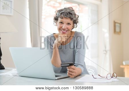 Happy senior woman making online payments of bill using laptop. Smiling mature woman shopping online with credit card. Pensioner holding credit card for internet banking and looking at camera.