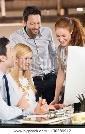 Group of happy smiling business people after gaining success in strategy. Manager briefing team members about their posts in office. Business team sitting at desk and planning work at office.