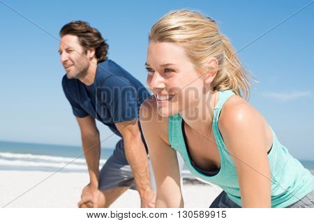 Young couple resting and looking away after a run on beach. Two young athletes ready to start a race. Couple having a break from running standing with their hands on knees.