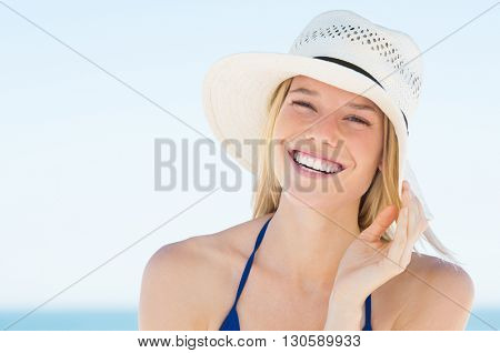 Portrait of smiling  woman on beach wearing blue bikini and straw hat. Close up face of beautiful yo