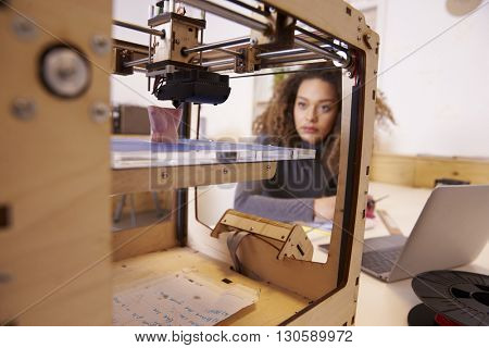 Female Designer Working With 3D Printer In Design Studio