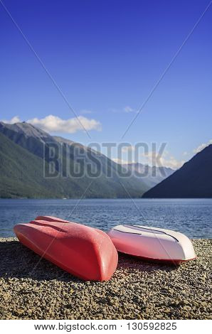 A beautiful recreation area with a couple colorful kayaks on shore lake