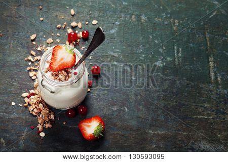 Healthy breakfast of muesli, berries with yogurt and seeds on dark background -  Healthy food, Diet, Detox, Clean Eating or Vegetarian concept.
