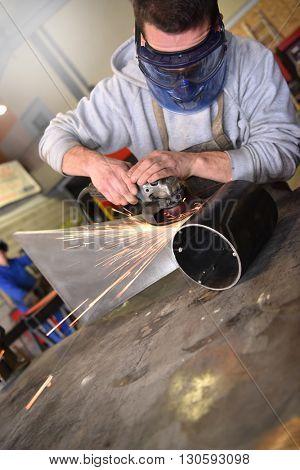 Metalworker in workshop welding piece of metal