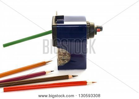 Colored pencils and large pencil sharpener on white background