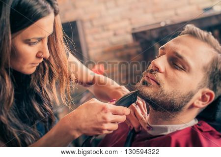 Female barber shaving a client's beard with trimmer in a barber shop