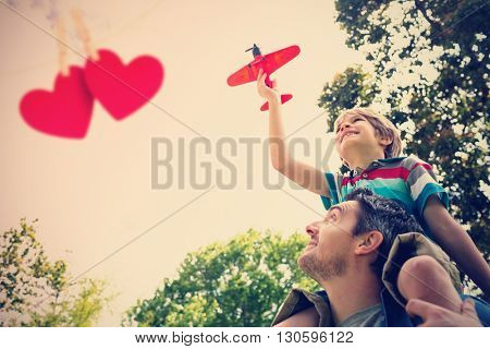 Boy with toy aeroplane sitting on fathers shoulders against hearts hanging on a line