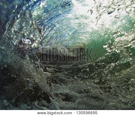 Inside a blue and green breaking wave in shallow water with sunlight shining through.