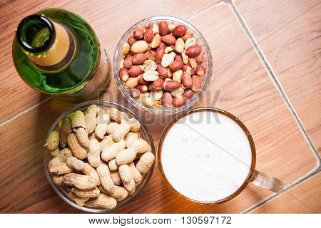 High Angle Still Life View Of Glass Of Cold Ale, Bottle Of Beer, Bowl Of Peanuts And Bottle  On Rust
