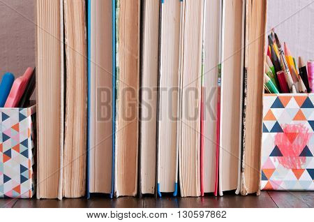 row of old yellowed books standing on a wooden shelf backed with pencels boxes brushes and pens
