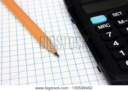 Black Calculator with pencil on grid notebook