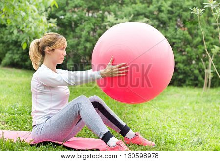 Girl Lifting Fitball In Garden