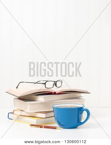 Small stack of textbooks and a cup of fresh coffee.