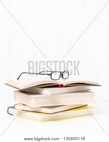 Small stack of hardcover books with eyeglasses sitting on top.