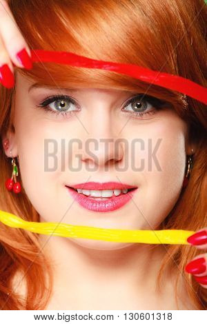 Sexy young woman holding candy. Redhair cute funny girl framing her face with sweet jelly on green