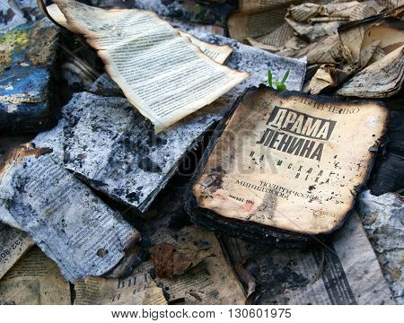 MOSCOW, RUSSIA - MAY 11, 2016: The old book titled Lenin's drama burnt in the fire at Krutitskoye podvorye lying on a pile of burnt papers in ruins