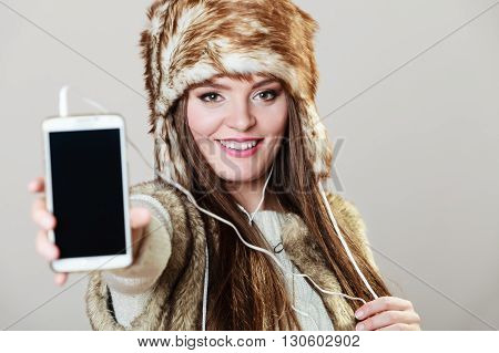 Winter girl listening music using phone with headphones showing blank screen. Happy woman wearing fur vest and warm hat in freezing cold time.