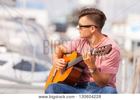Romantic music sound masculine concept. Young man playing guitar. Boy sitting on pier playing on instrument.