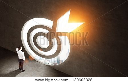 Targeting concept with thoughtful businessman looking at sunlit city view through dartboard opening in concrete wall