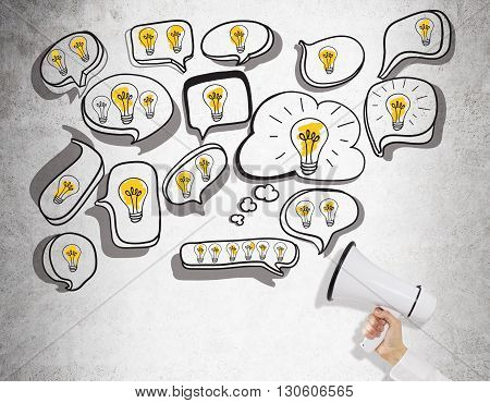 Idea concept with lightbulbs in speech and thought bubbles and businessman hand holding megaphone on concrete background