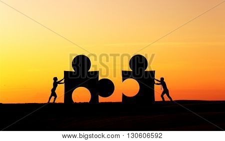 Partnership concept with businesspeople silhouettes putting puzzle pieces together at sunset