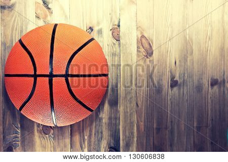 Basketball ball on wooden hardwood floor in the basketball court. Retro vintage picture. Sport concept.