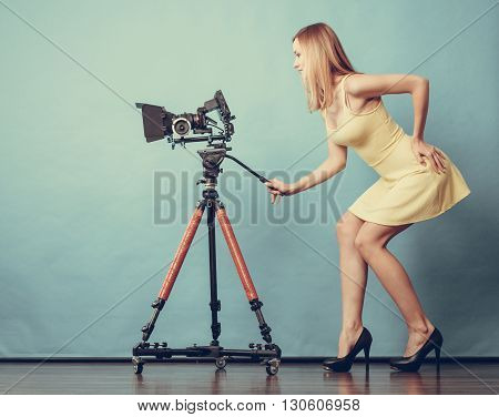 Photographer girl shooting images. Attractive fashionable blonde woman in full length taking photos with camera on blue