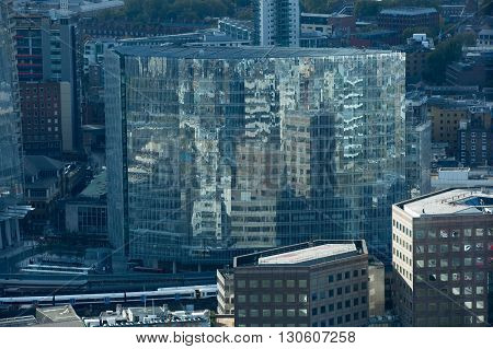 LONDON, UK - OCTOBER 14, 2015. Office corporate buildings glass reflection, view on the Shard of glass and London bridge train station