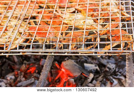 Grilled crab on flaming grill. Charcoal fire grill. Barbecue embers glowing in red fire.