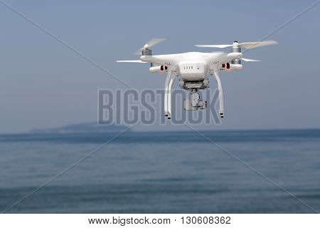 KAGAWA, JAPAN - MAY 06, 2016: White remote controlled Drone Dji Phantom 3 equipped with high resolution video camera hovering in air with beach.