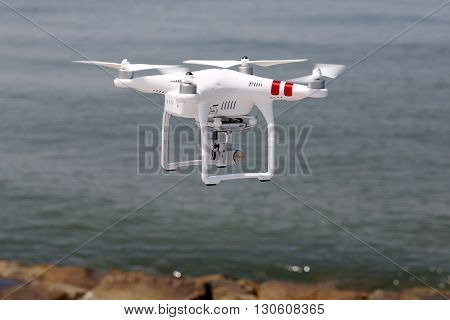 KAGAWA, JAPAN - MAY 06, 2016: White remote controlled Drone Dji Phantom 3 equipped with high resolution video camera hovering in air with beach