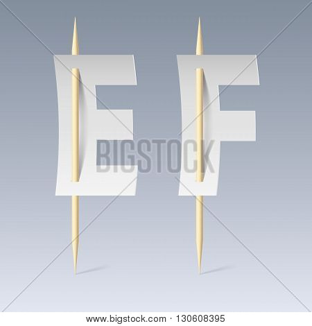 White paper cut font on toothpicks on grey background. E and F letters