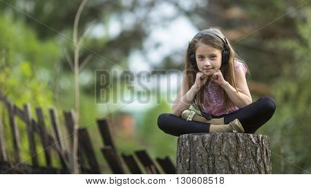 Little girl in headphones sitting thoughtfully outdoors.