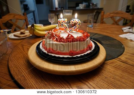 A birthday cake with lit candles on the dining room table of a home in Harbor Springs, Michigan.