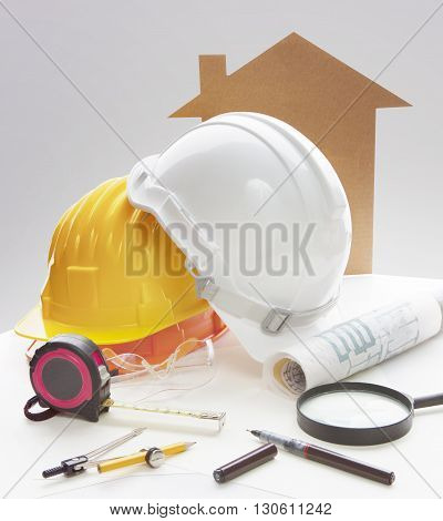 engineering working table writing tool equipment and safety helmet against two point perspective of building exterior