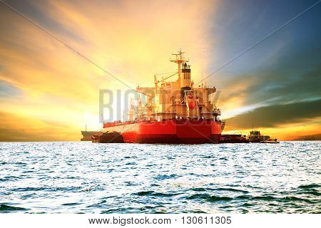 commercial container ship loading goods in sea harbor port against beautiful sun light