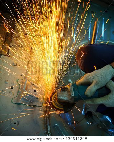 industrial metal cutting tool in iron factory shop working and cut on steel sheet against beautiful fire sparking