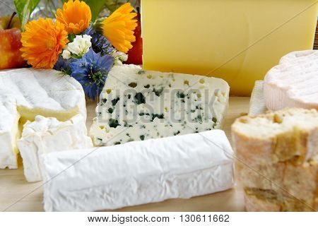 a tray with different French cheeses with flowers