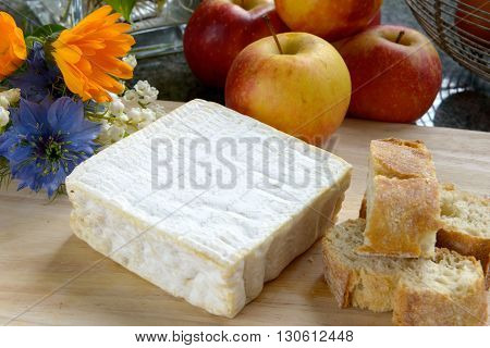 a tray with pont eveque cheese with bread and apples