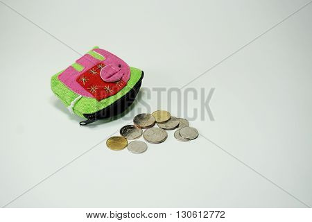 Coins falling from purse isoltaed on white background