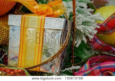 Box and ribbon Christmas tree ornament. Silver gift box and yellow-orange ribbon netting. Closeup view.
