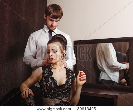 Married couple. Romantic evening at the hotel. Love and passion. Men wear a necklace around the neck of his wife.