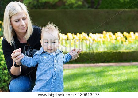 laughing cute toddler boy with his young beautiful mother making first steps enjoying time together in the park